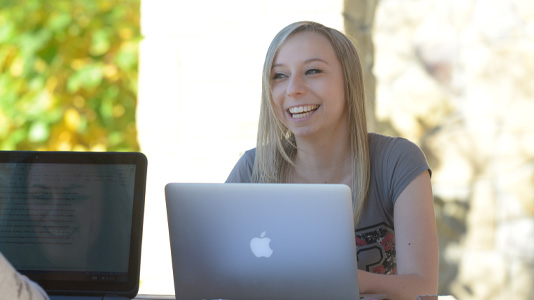A student sitting outside at a picnic table in front of a laptop smiling.