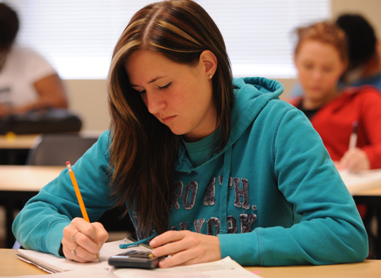 A student ;using a calculator to complete an in-class assignment