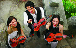 picture of the fitzgeralds music group holding violins and laughing