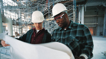 Two men standing in front of a job site reading blue prints.